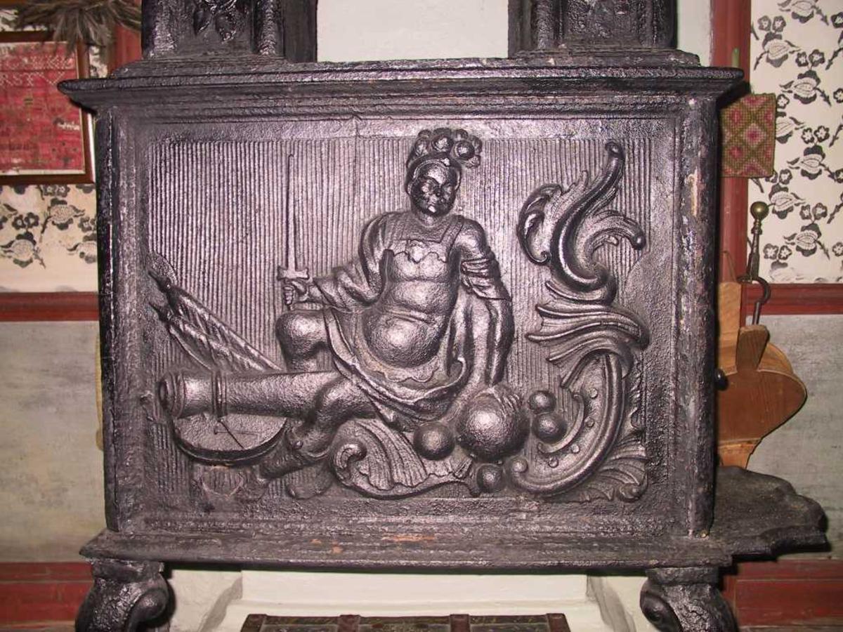 Krigsguden Mars, sittende på kanon med sverd i høyre hånd og en kanonkule i venstre. rokokkoornamenter.