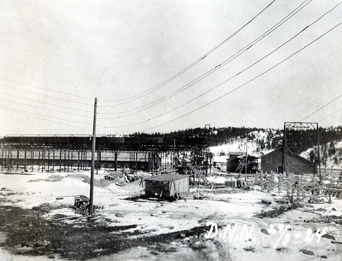 """""""29/03-1924"""" Nitriden. Bygging av stekeribygning for steking av elektrodekull. Jernkonstruksjoner. Kraner på kai og lagerbygning for bauxitt. Taubanemast. Bærende konstruksjoner for """"høybanen"""". Skinnegang for intern transport med traller trukket av dieseldrevet lokomotiv. Tromøysund og Tromøy i bakgrunnen."""