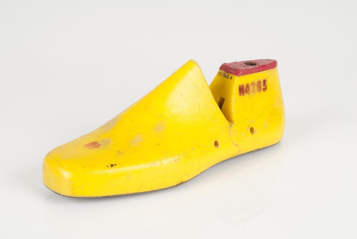 En plastmodell (lest) i fargen gul. Venstrefot i skostørrelse 40. Såle i metall.