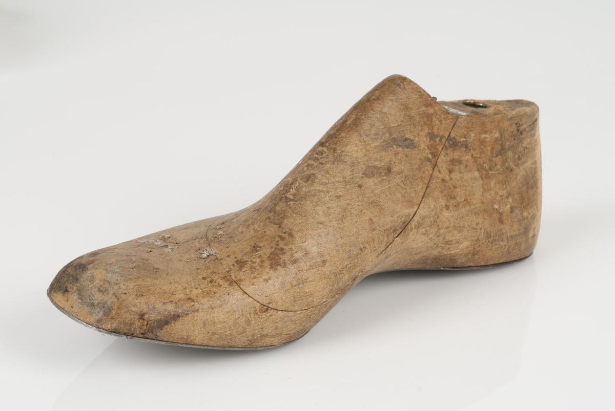 En tremodell i to deler; lest og opplest/overlest (kile). Høyrefot i skostørrelse 35, og 8 cm i vidde. Såle av metall.