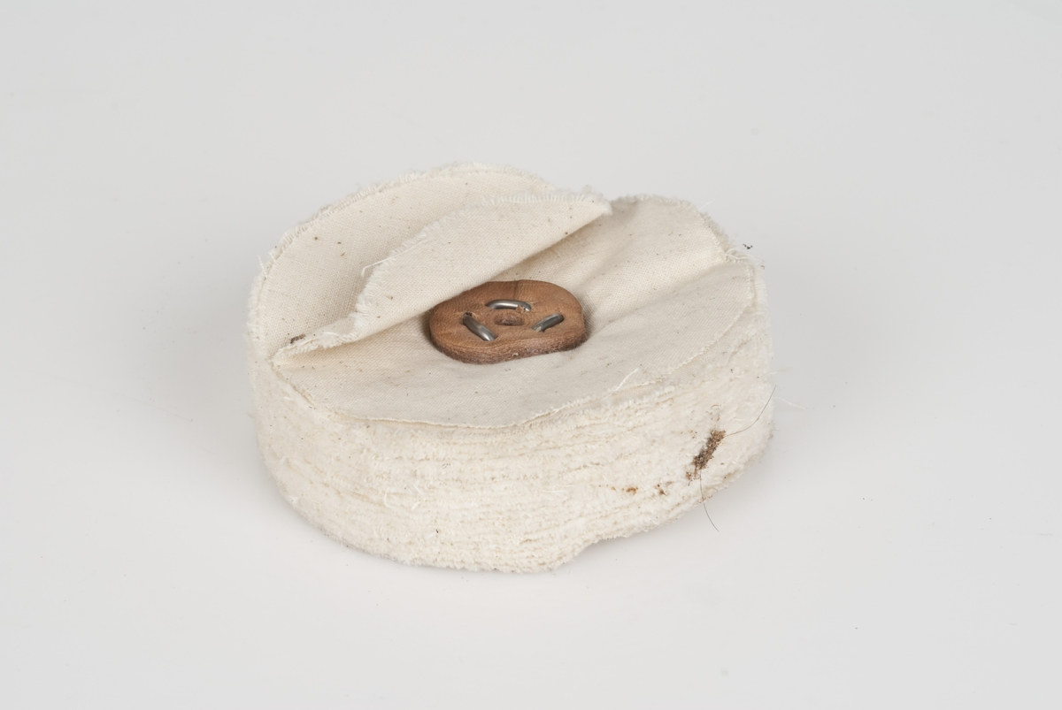 En rund poleringsmop til pussemaskin. Poleringsmopen er av hvit tekstil. Skinnfeste på hver side.