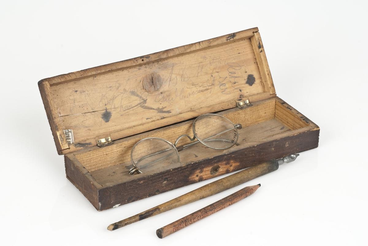 En rektangulær treboks (A) med lesebriller, blekkpenn og blyant i. Lesebriller (B) av metall og glass. Blekkpenn (C) av metall og tre. Blyant (D) av bly og tre.