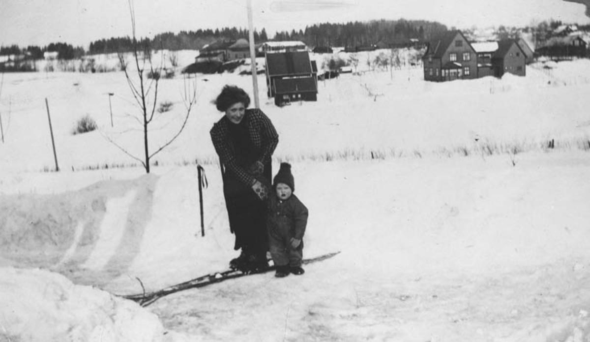 Utsikt mot lokomotivstallen på Ski. Dame med lite barn på ski.