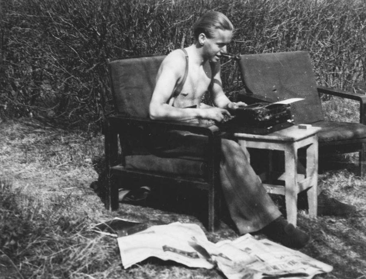 Ung gutt skriver på skrivemaskin i hagen.