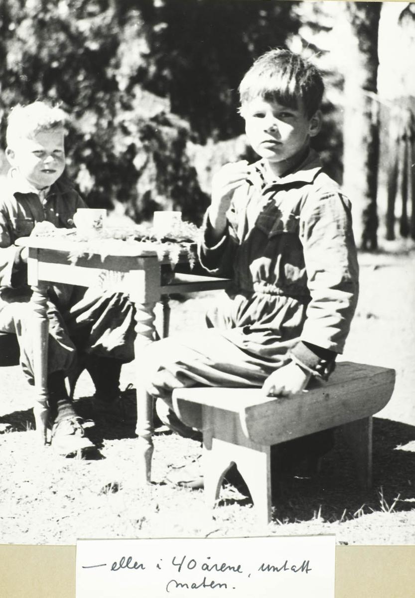 To barn sittende på skamler og spiser utendørs.