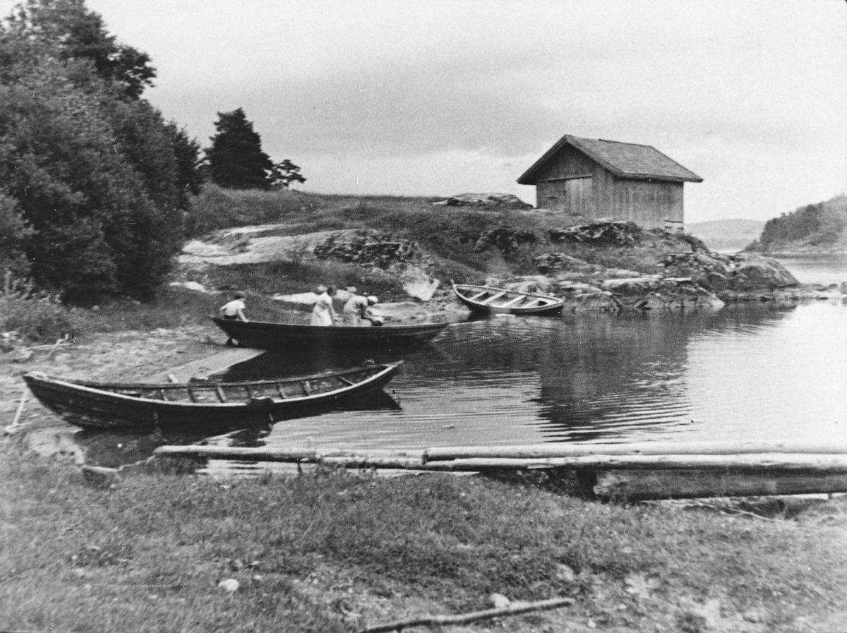 Preståa brygge ved Øyeren med 3 småbåter ved vannet. en gutt og 2 kvinner ved den ene.