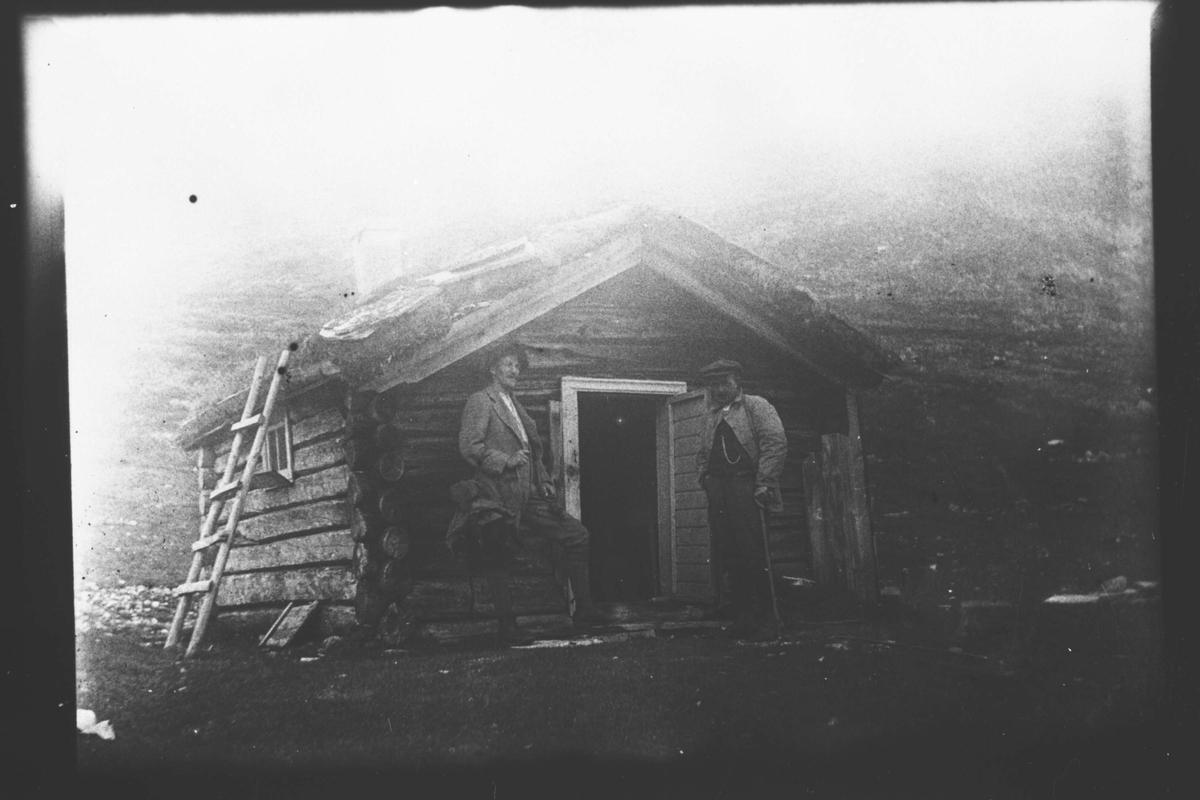 To menn foran en hytte