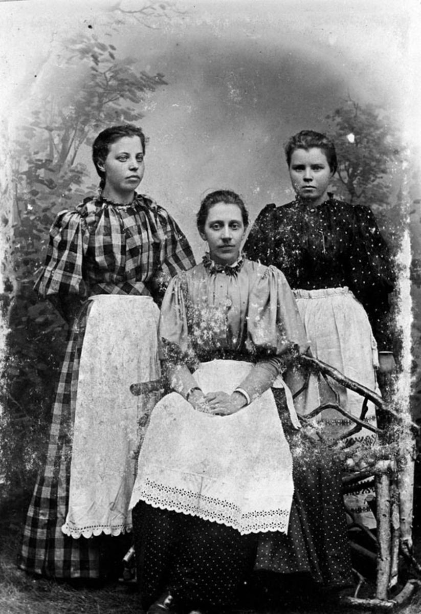 Atelierbilde av tre yngre kvinner m/lange kjoler og forklær.