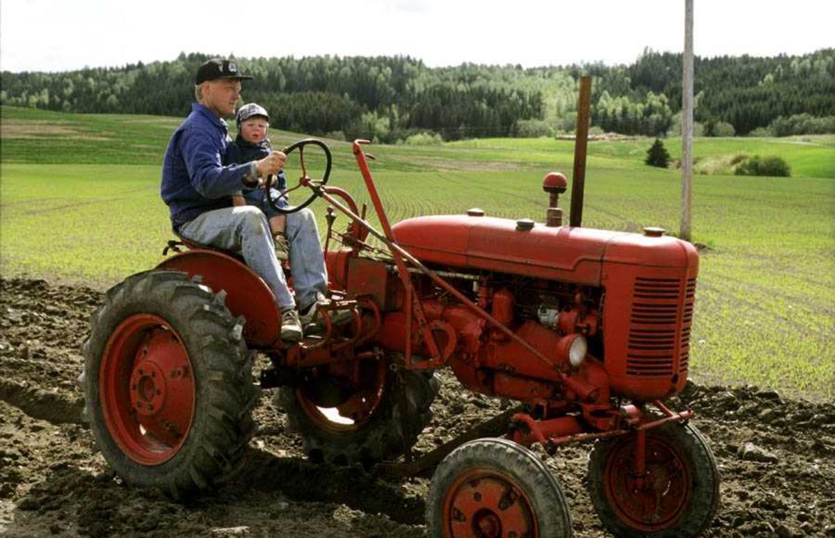 """Dokumentasjon av drenering i forbindelse med åpning av ny utstilling: """"Jordbrukets utvikling på Romerike"""" på Gamle Hvam. Bruk av dreneringsredskaper. Demonstrering av drenering. Mann på traktor (Christoffer Hønsen) med sønn."""