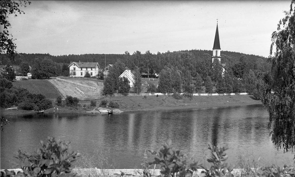Kirke og gårdsbruk ved en elv.