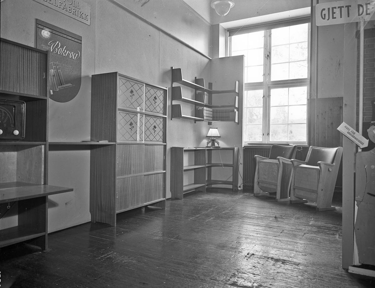 """Fra Eidsvoll Bygdeutstilling i 1955,  Eidsvoll Møbelfabrikk. Utstilling av """"Bokroa – bøkenes byggmester"""" skap- og hyllesystem. """"Norsk Patent nr. 82660"""". """"Den moderne byggereol for hjem og kontor."""""""