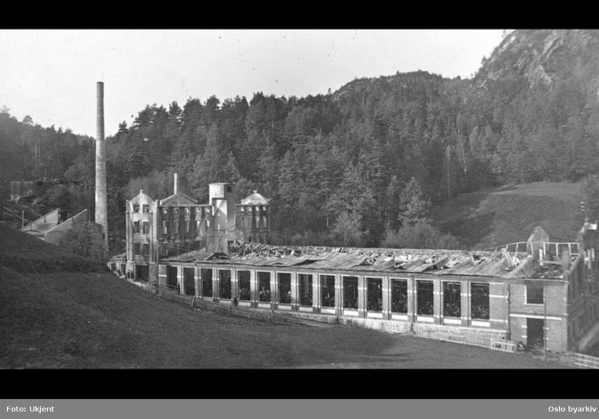 Postkortfotografi av nedbrent tekstilfabrikk. Sannsynlig Høie fabrikker i Kristiansand