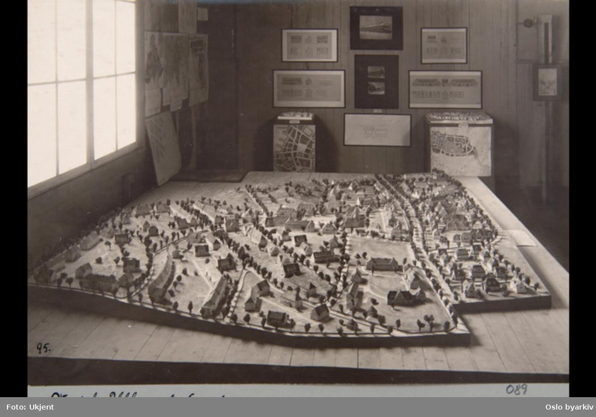 """Modell av Ullevål Hageby. Tegninger og foto på veggen. Sannsynligvis fra 1920-tallet. Albumtittel: """"Fotografier over Kristiania kommunes boligbebyggelse""""."""