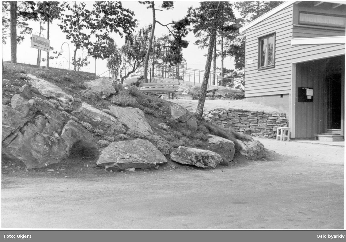 Ved inngangen til administrasjons / kontorbygningen på Ingierstrand bad. Skilt på høyden viser veien til dampskipsbrygga.