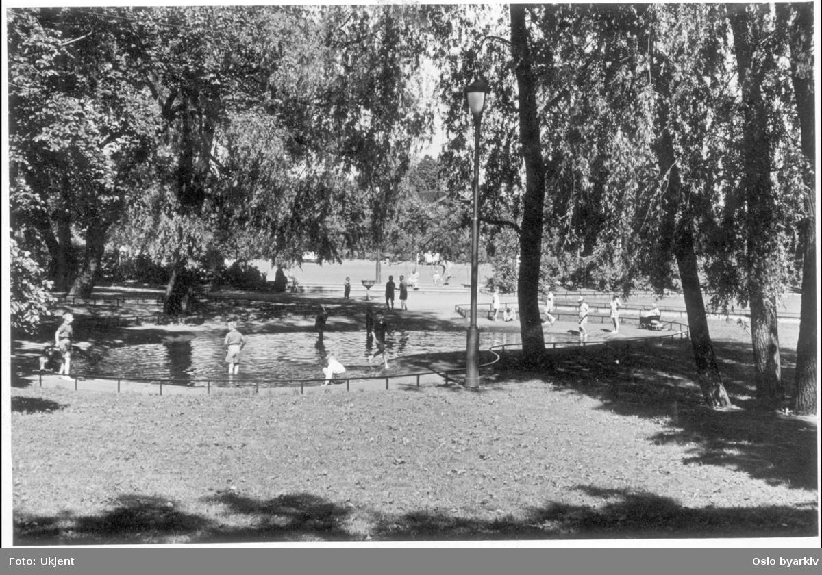 Fra sørøstre Kampen park. Barn i lek ved bassenget / plaskedammen mellom Bøgata og Sons gate (tidl. Vestbygata). Parktrær.