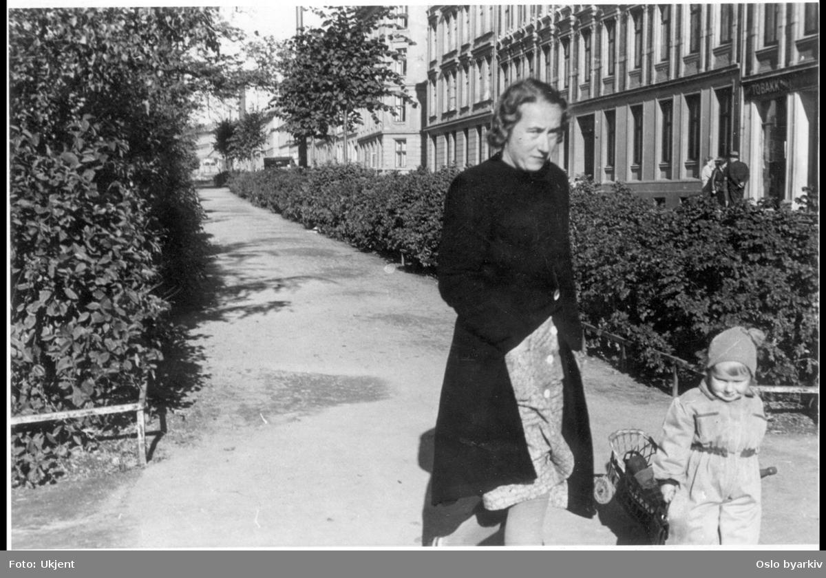 Mor med barn på gangvei langs Grünerhagen. Fra Nordre gate i syd og nordover, med Fossveiens endeløse bygårdsrekke til høyre i bildet. Frukt og tobakkbutikk i gården. Sannert til fordel for bolig og forretningskomplekset Grünerbygg (1979).
