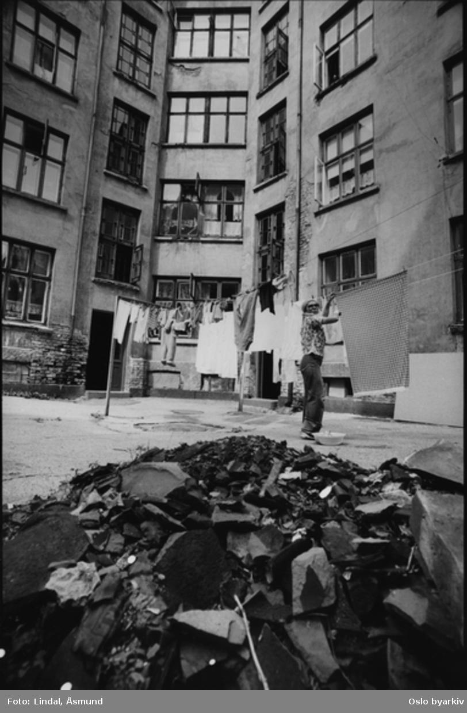 Klesvask til tørk i bakgården. Kvinne henger opp tøy. Fotografiet er fra prosjektet og boka ''Oslo-bilder. En fotografisk dokumentasjon av bo og leveforhold i 1981 - 82''. Kontakt Samfoto ved ev. bestilling av kopier.
