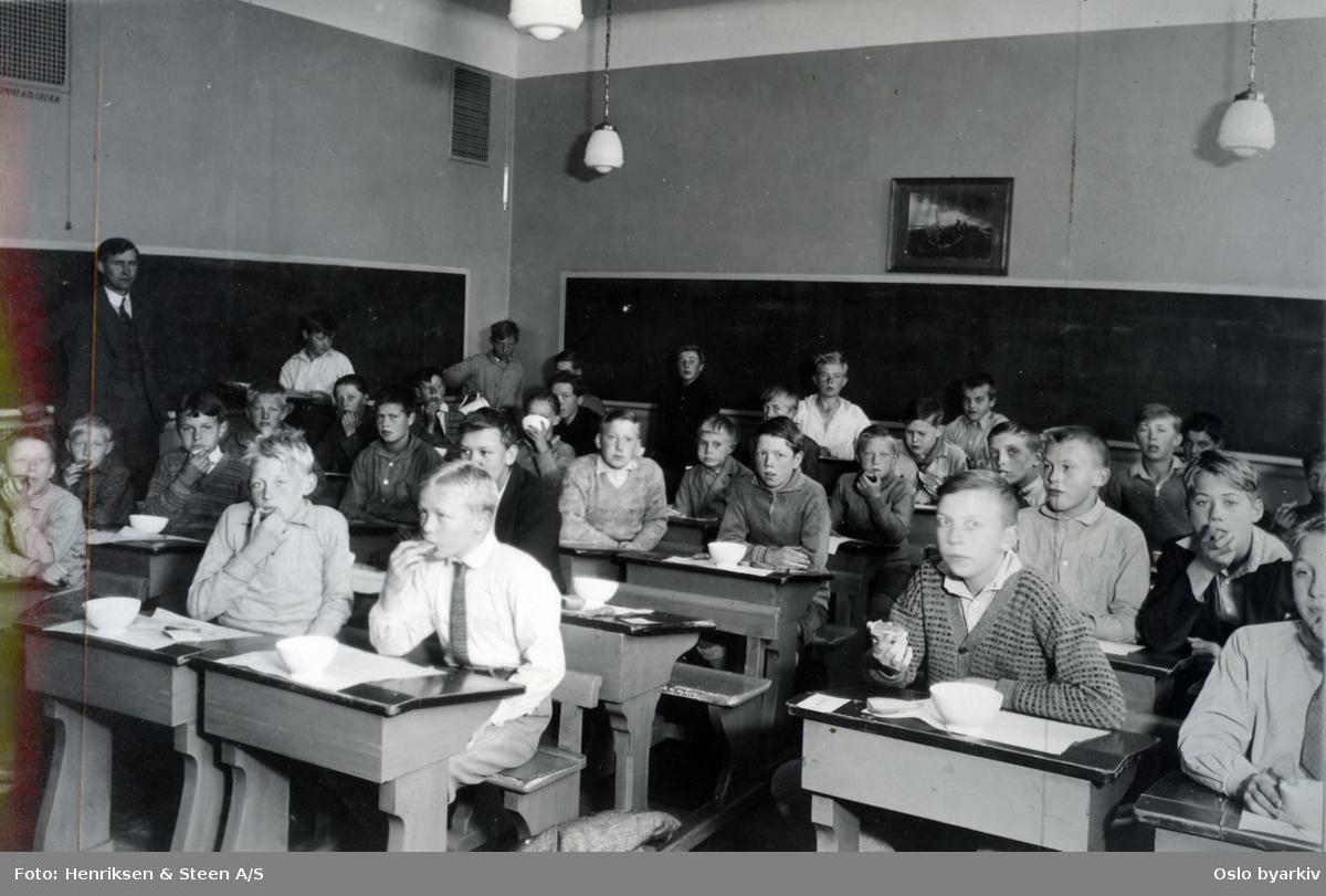 Skoleklasse. Skolefrokost i klasserommet. Elevene ved pultene med mat og melkeflasker. Oslofrokost.