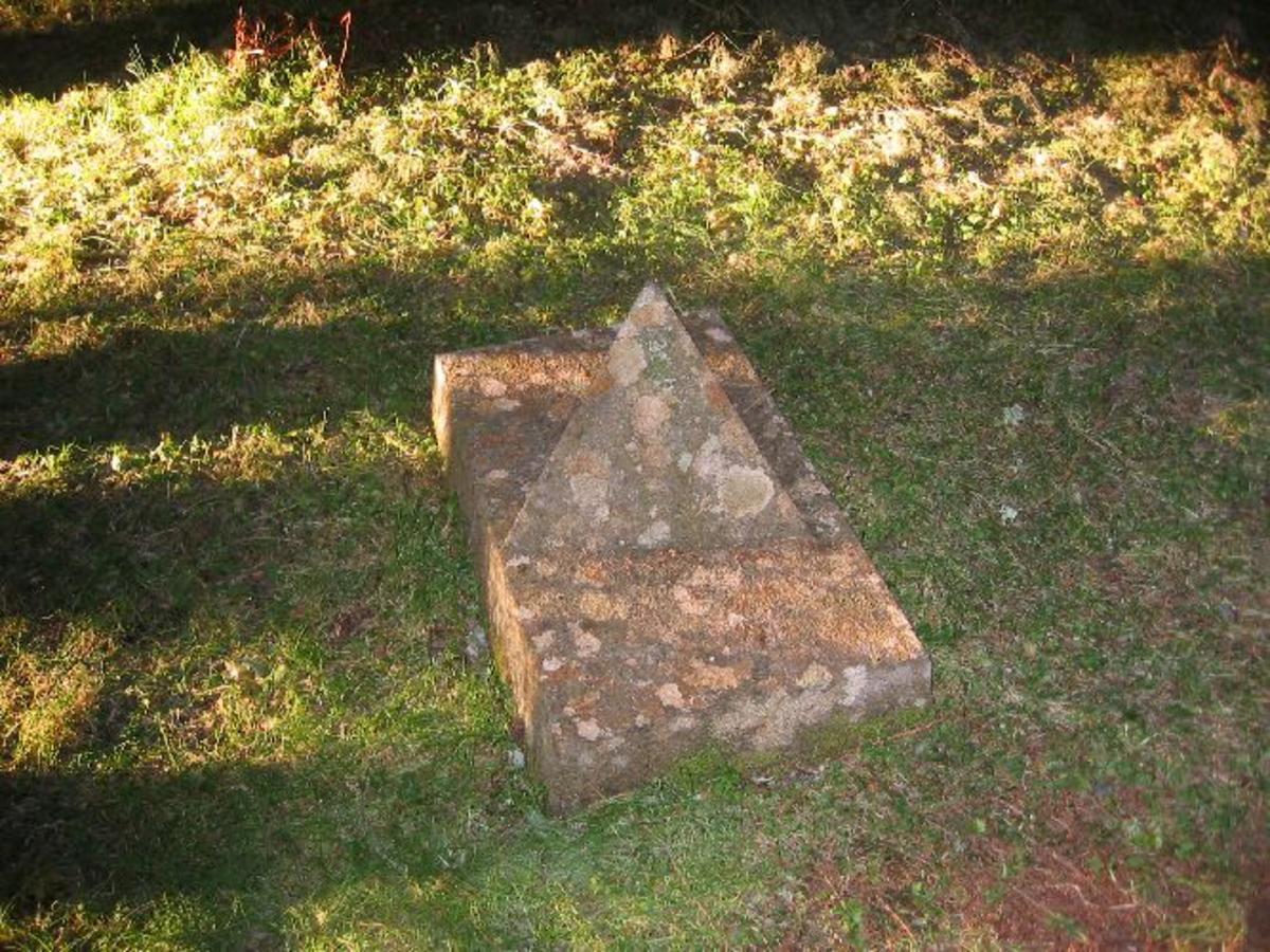 Tilhugget trekantig pyramide plassert på sokkel av tilhugget stein. Dette er nr. 15 av 27.
