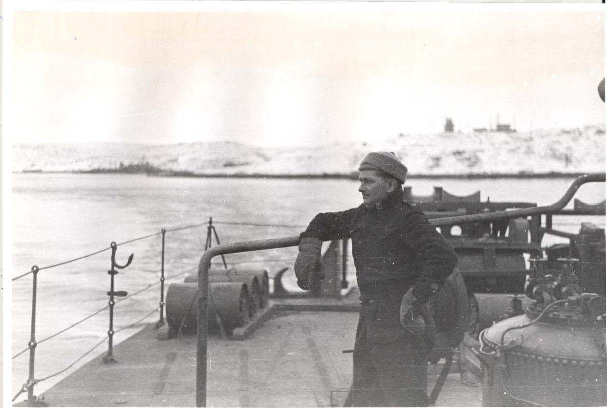 """Enkeltbilde. Jageren Stord i konvoy til Murmansk. Bildet er tatt da """"Stord"""" nærmer seg Murmansk. Kvartermester Andersen står på dekk."""