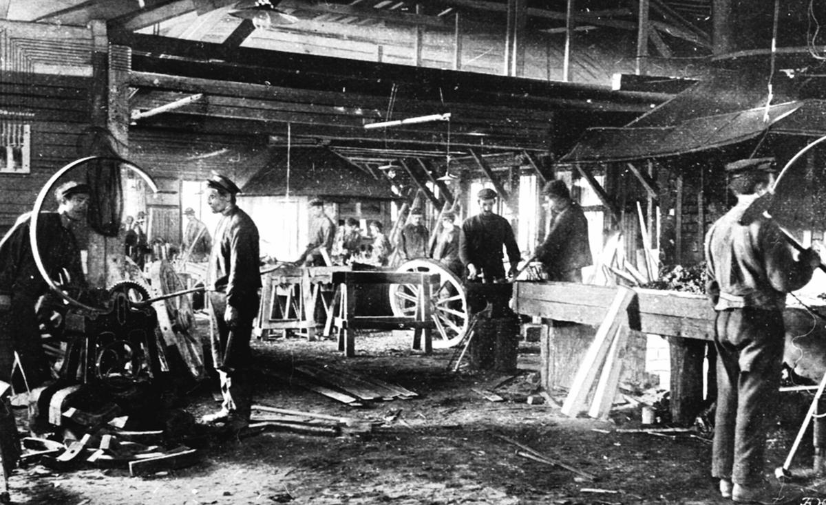 Interiør, smie ved Moelven Brug, Ringsaker. Smeder i arbeid med å jernbeslå kjerrehjul.