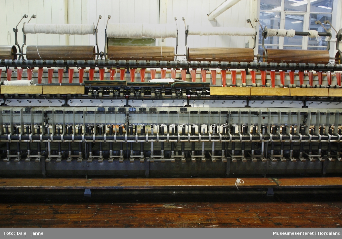 """Elektrisk ringspinnemaskin (1958) frå det sveitsiske selskapet Rieter. Øvst på maskina plasserer ein spolane med forgarn frå kardemaskina. Reint teknisk er det tre hovudelement i spinninga:  forgarnet blir strukke, tvista (snodd) for å få meir styrke, før det ferdige garnet blir oppvikla på ein spole eller 'spinnepipe'. Tråden går under eit transporthjul i tre, gjennom støypte løpegangar og vidare nedover: Garnet blir snodd ved at garnet passerer ein løpar som beveger seg på ein ring, før det blir samla på ein sylindrisk metallspole. Det er ei rekkje små støvsugarar langs heile maskina, små røyr som stikk ut over spolane. Desse syg til seg støv og/eller tråden viss den ryk, for å unngå at den kjem inn i maskina. Trådrestar og støv blir samla opp i eit oppsamlingskammer på venstre sida av maskina. Der er det òg ein målar som måler kor mykje maskina spinner.  Drivverket og ein stjernemotor sit på høgre sida av maskina. På sida står det """"Rieter"""" i raudt, og det er to målarar som måler omdreiingar/hastigheit på maskina. Det er ei rekkje med 136 koner på kvar side. Maskina kan byggjast på i seksjonar, og slik utvidast etter behov, noko som er vanleg for spinne- og spolemaskiner."""