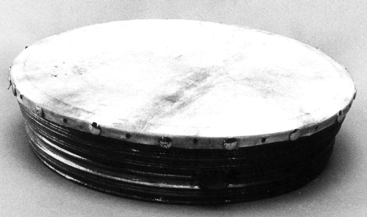 Rammetromme av profilert brunt tre. Membran av hud er stiftet til rammen. Tre tredoble små cymbaler er festet med strenger i åpninger i rammen.