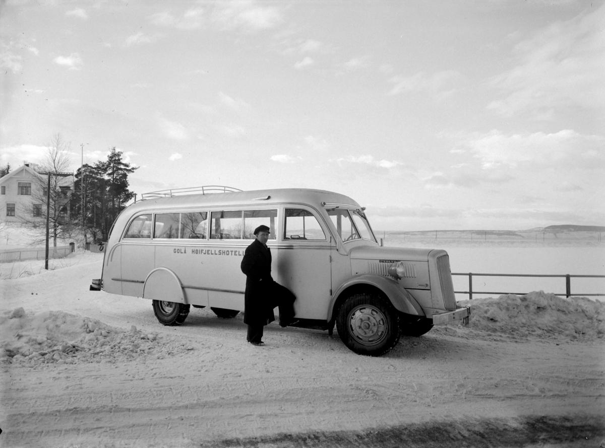 """JORDKJEND, MANN + BUSS M/ """"GOLÅ HØIFJELLSHOTELL"""" Sjåføren er min far, Ludvig Graff fra Hundorp. 1894-1965. Han jobbet på Golå i 30-35 år.  Bussen er en Volvo 1936. karosseriet ble laget av Kristiansand Karosserifabrikk. Den gikk i fast rute mellom Harpefoss og Golå fra ca 1936 til ca 1960. Min far hadde rutevognbevilgning på strekket. Under krigen gikk den på gengass (knott). Den ble vedlikeholdt av far og Jakop Kleiven, Otta.  Dekkslene over bakjulene forsvant fort, og den fikk også støtfanger med plogfeste foran.  Bildet er tatt ved Stangebrua, Hamar/Stange."""