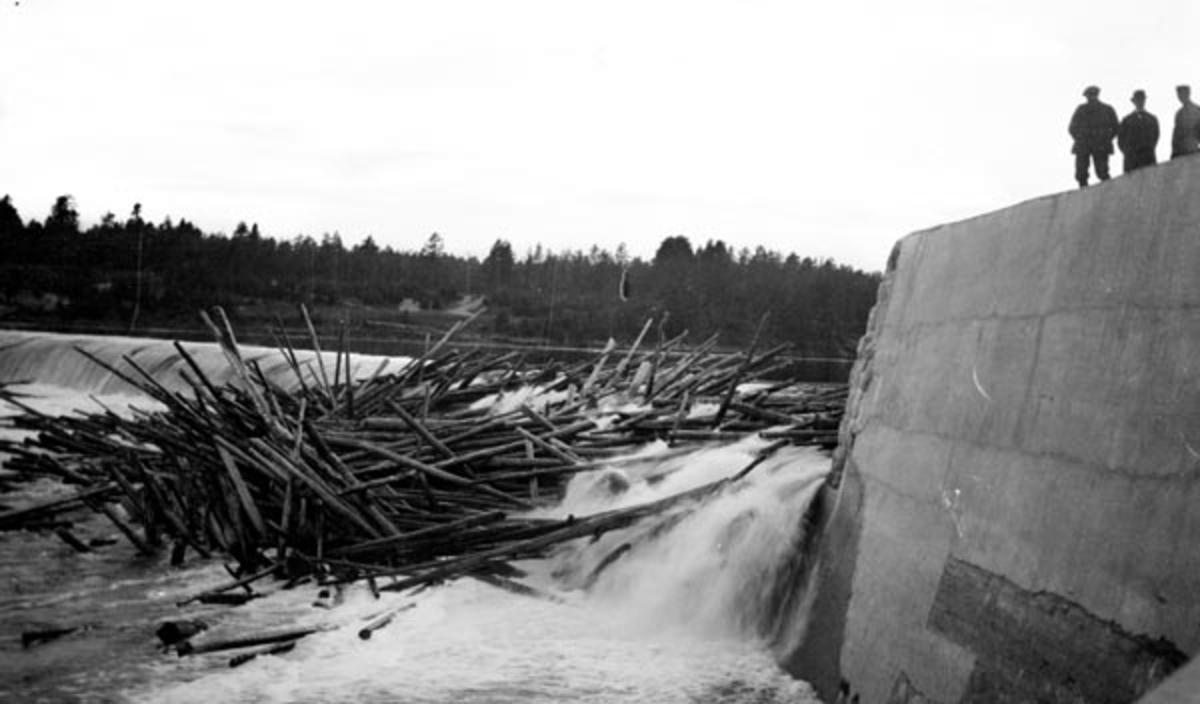 Haugdannelse ved dammen i Skjefstadfossen i Glomma.  Skjefstafossen ligger i Heradsbygda i Elverum, hvor det første store kraftutbyggingsprosjektet i denne delen av vassdraget ble realisert i 1909-1910.  Det er grunn til å tro at dette fotografiet ble tatt den første fløtingssesongen etter at dammen var ferdigstilt.  Fotografen har stått like nedenfor dammen, i ly av et kraftig landkar av betong.  Oppå denne konstruksjonen sto det tre karer i samtale da fotografiet ble tatt, sannsynligvis i samband med ei befaring.  I elveløpet, under den østre delen av den buete, drøyt 300 meter lange betongdammen, har det filtret seg sammen en del fløtingsvirke.  Å løsne en tømmervase på et slikt sted mens vannføringa ennå var stor nok til at stokkene lett lot seg fløte videre nedover vassdraget, var både farlig for arbeiderne og kostbart for fløtingsforeningen.  Det er sannsynlig at fotografiet er tatt nettopp for å dokumentere slike problemer overfor selskapet som hadde stått bak utbyggingsprosjektet, og som dermed var ansvarlig for å holde andre aktører som hadde hevd på bruken av vassdraget skadesløse.   Litt mer informasjon om kraftanlegget ved Skjefstadfossen finnes under fanen «Andre opplysninger».