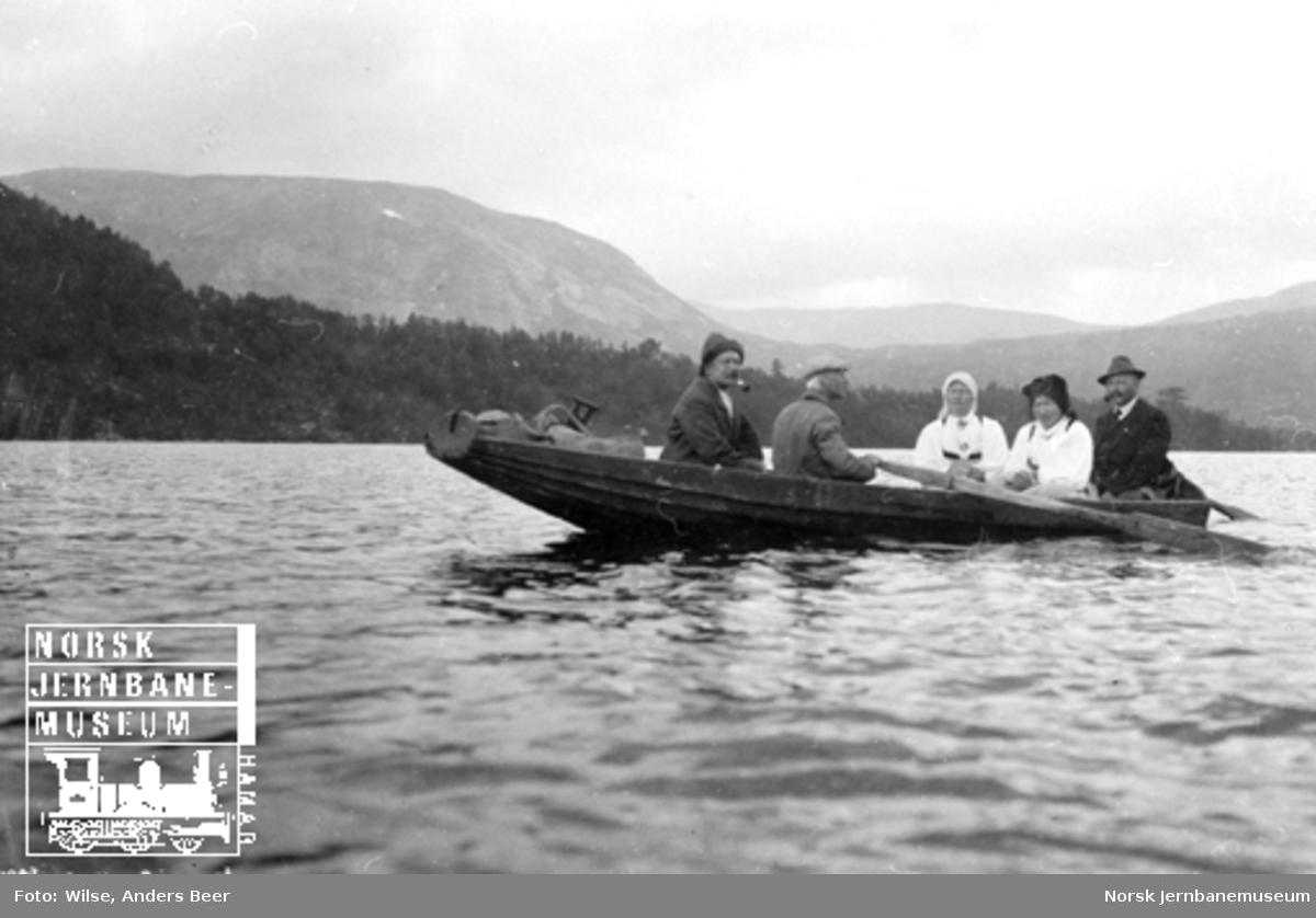 Fem personer, hvorav to kvinner i bunad, i robåt på Store Bjørnevatn i Setesdal