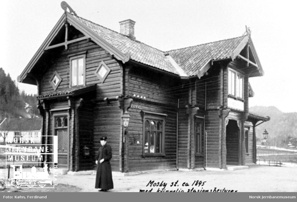 Mosby stasjonsbygning med kvinnelig ekspeditør på plattformen