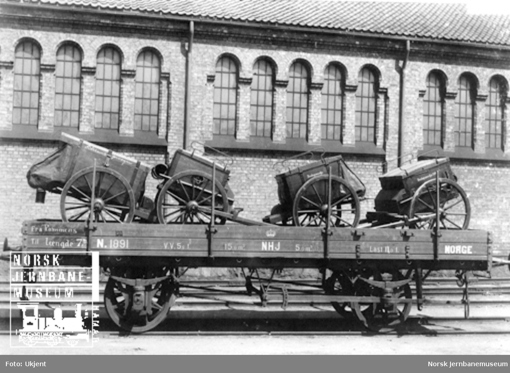 Hovedbanens vogn litra N nr. 1891 lastet med artillerimateriell; bøssemakervogn og beslagsmakervogn
