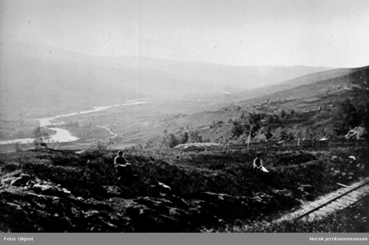 Parti med jernbanen og dalen sør for Ålen; to menn sitter ved siden av sporet