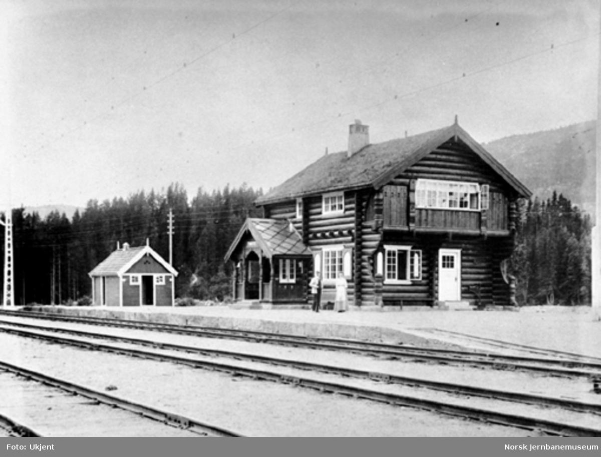 Tinnoset stasjon med stasjonsbygning og privet; to personer på plattformen