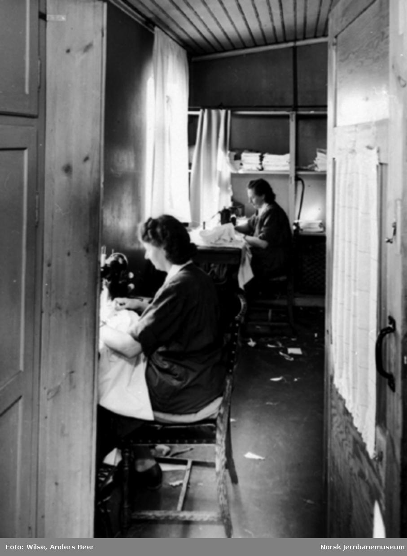 To kvinner med symaskiner lapper sovevognstøy