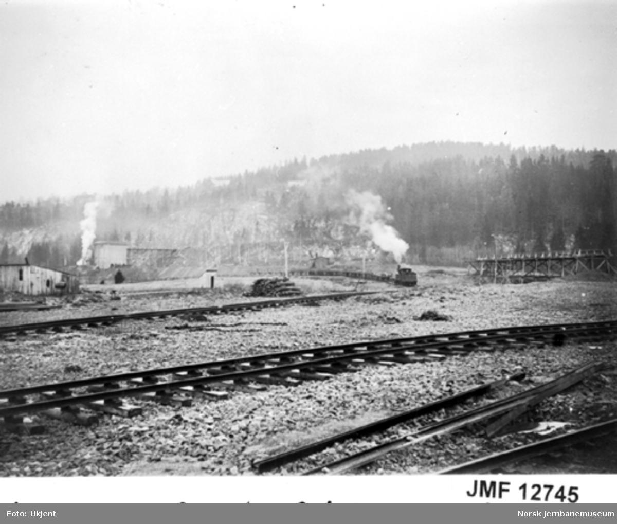 Et damplokomotiv med pukktog kjører ut fra pukkverket og pukksteinslageret på Grorud