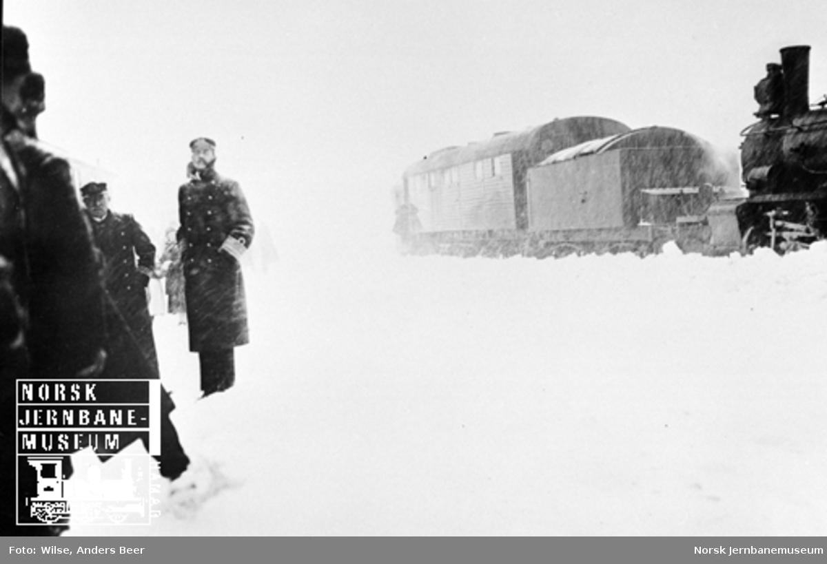 Kong Haakon på Finse stasjon ved Bergensbanens åpning. Roterende snøplog i bakgrunnen