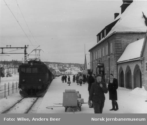 Kongsberg stasjon, persontog trukket av elektrisk lokomotiv El 8 ankommer, reisende på plattformen