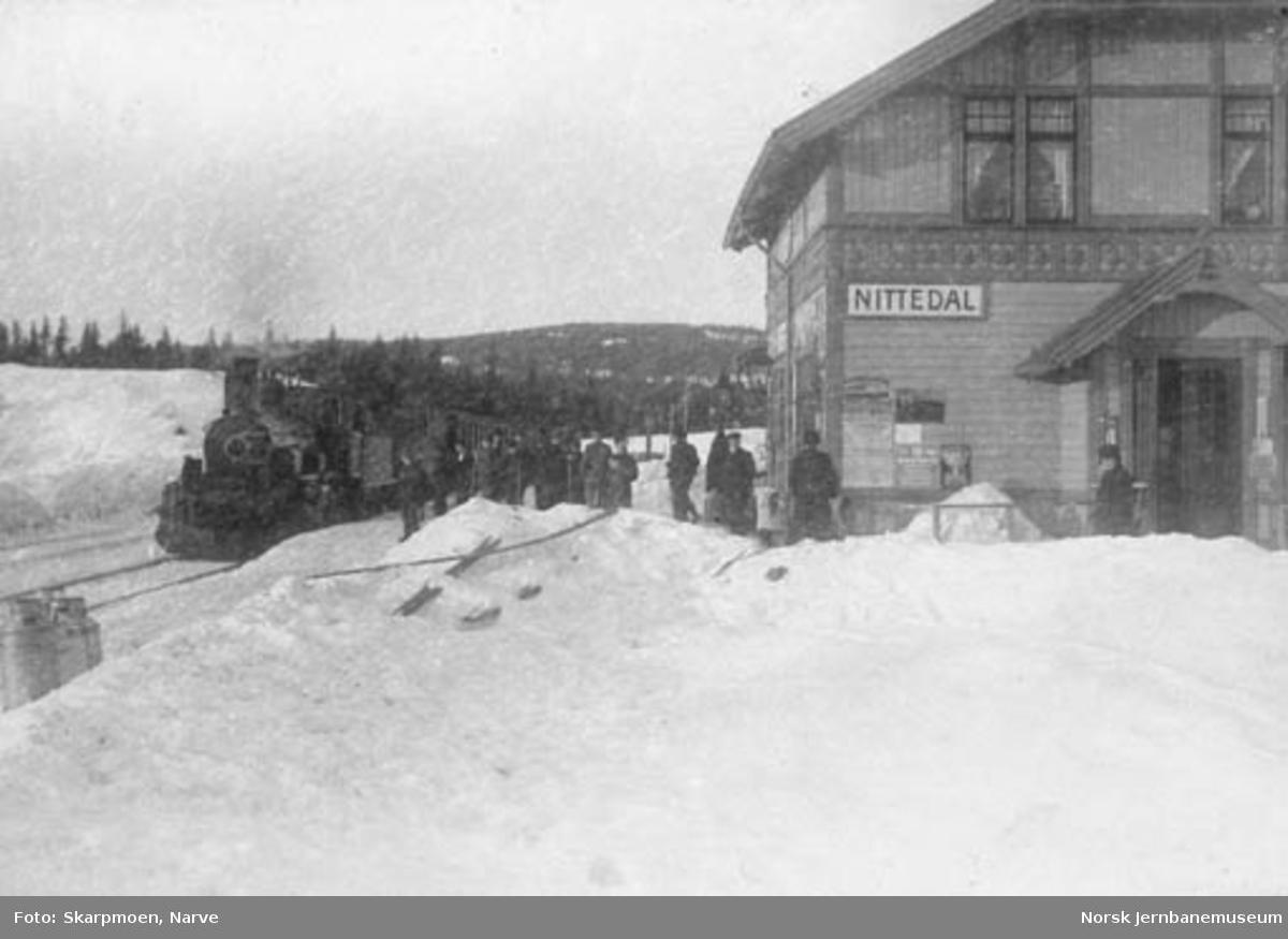 Nittedal stasjon med skiløpere på plattformen og ankommende tog