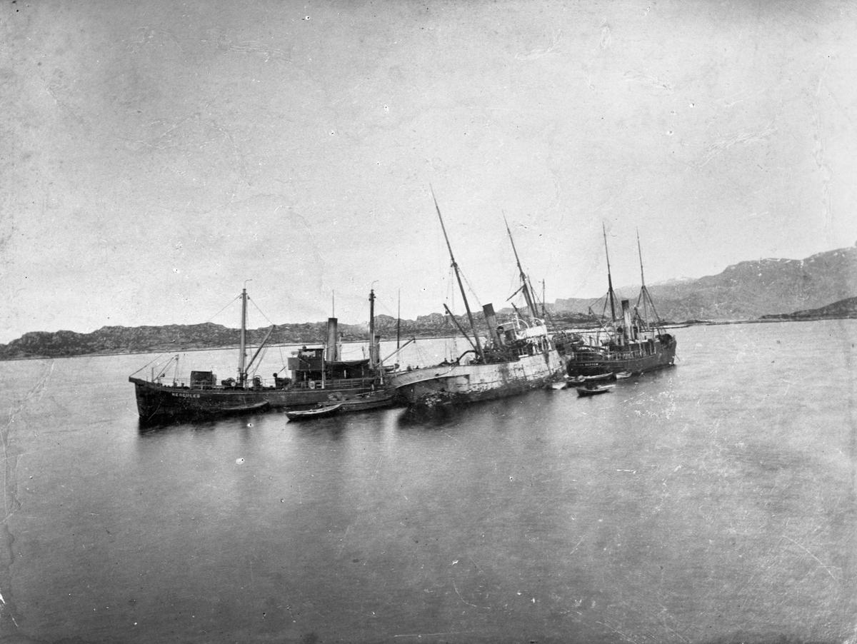 """Dampskipet D/S """"Aalesund"""" har gått på et skjær. Deler av mannskapet på dekk. To andre skip, """"Hercules"""" til venstre, og et annet skip til høyre. To mindre båter foran skipene. Land og fjell i bakgrunnen."""