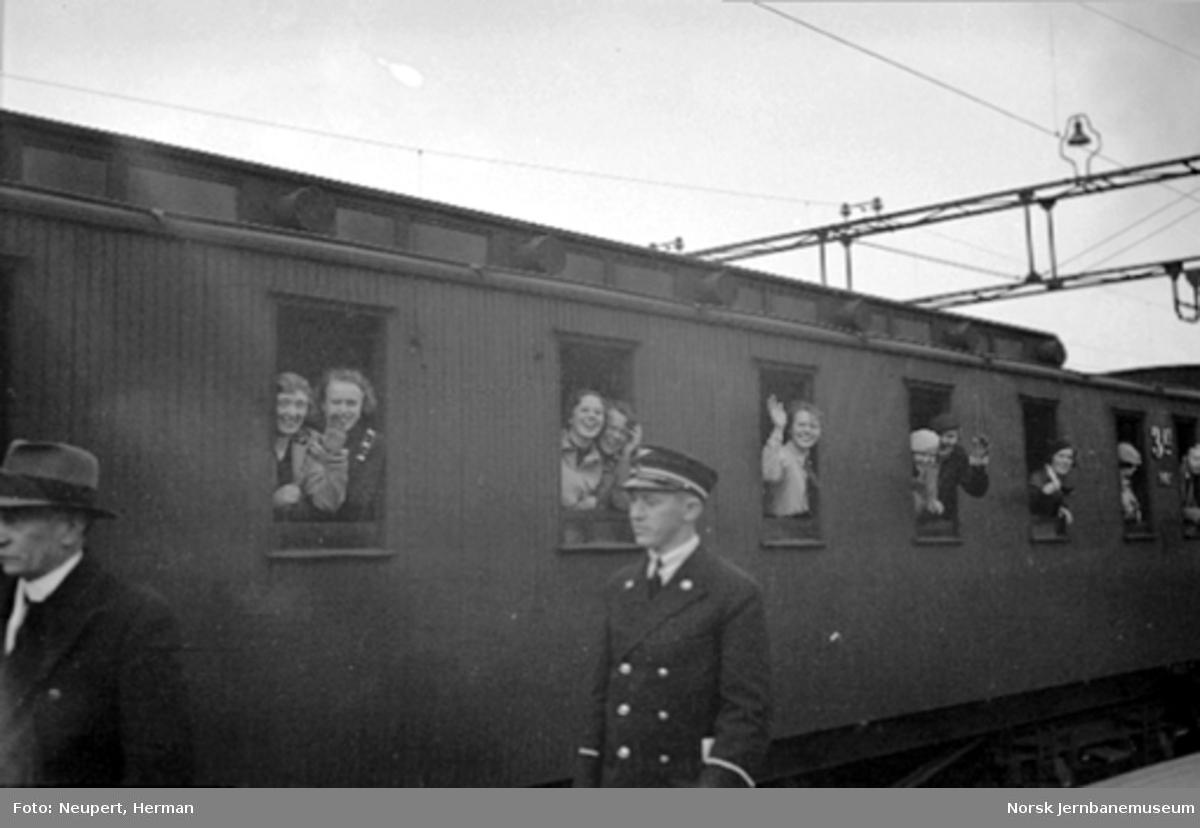 Reisende i vinduene på en personvogn på Oslo Østbanestasjon