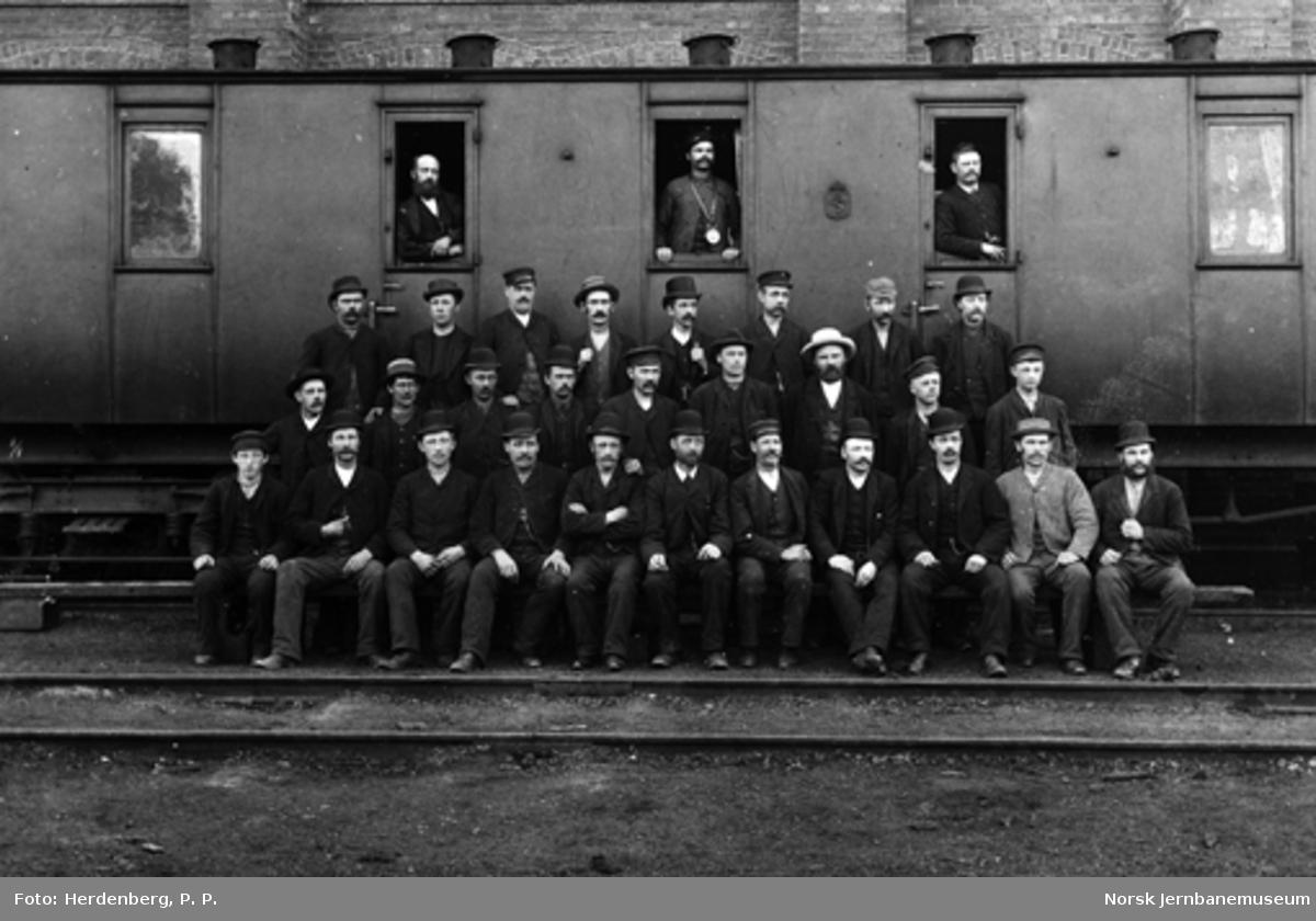 Gruppebilde av ansatte foran en personvogn