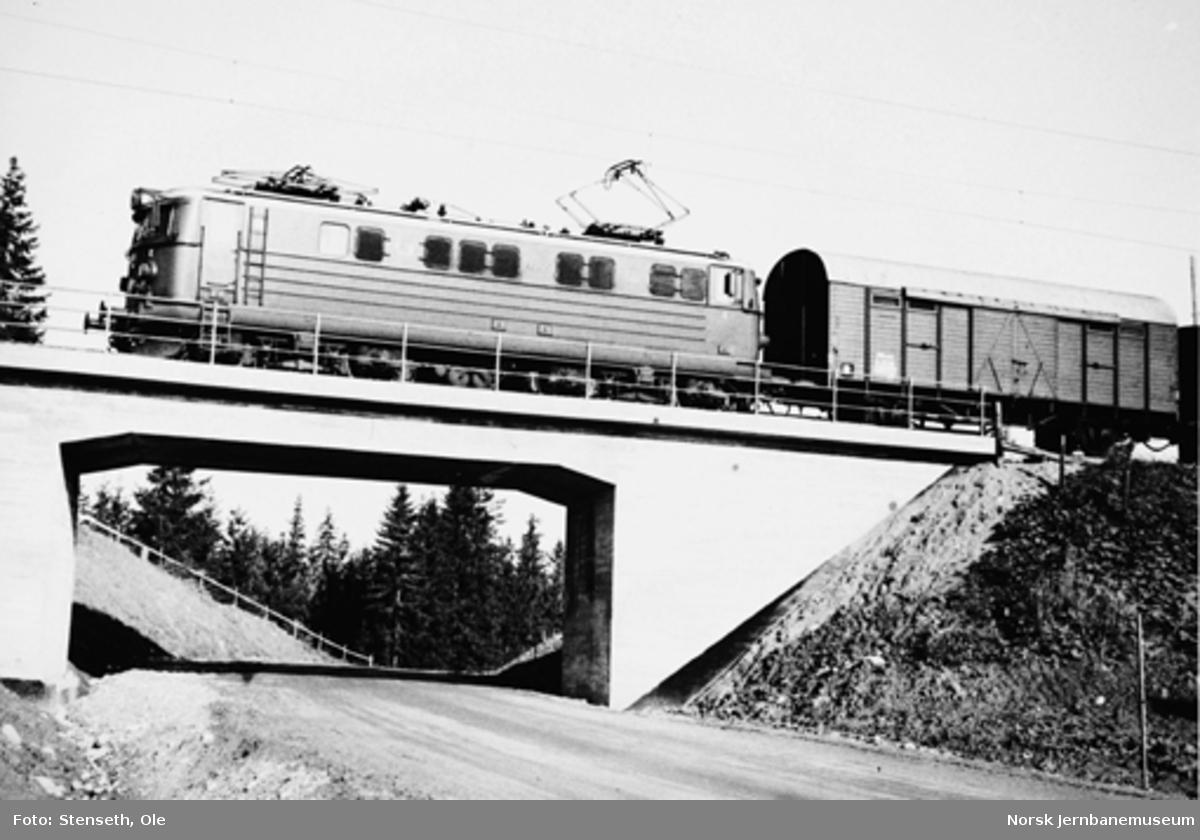 Elektrisk lokomotiv type El 13 med godstog passerer en nyanlagt vegundergang