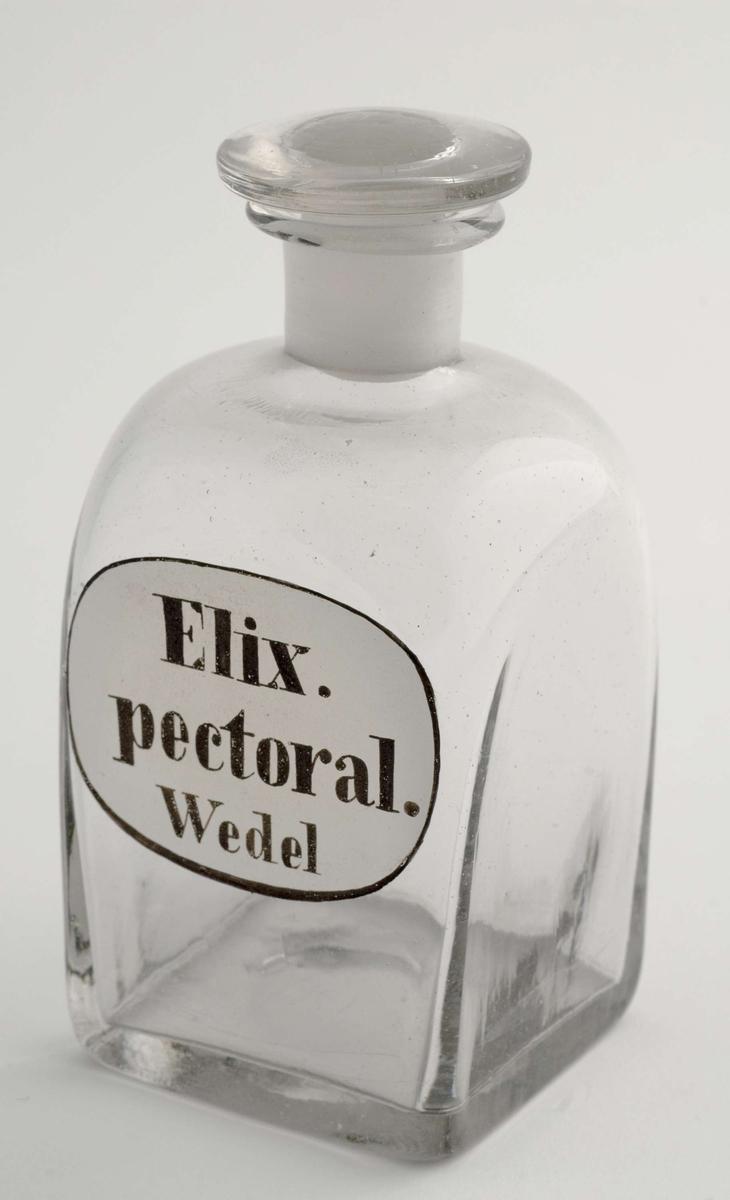 Klart firkantet standglass med rund propp. Oval, hvit emaljert etikett med sort kant og sort skrift.