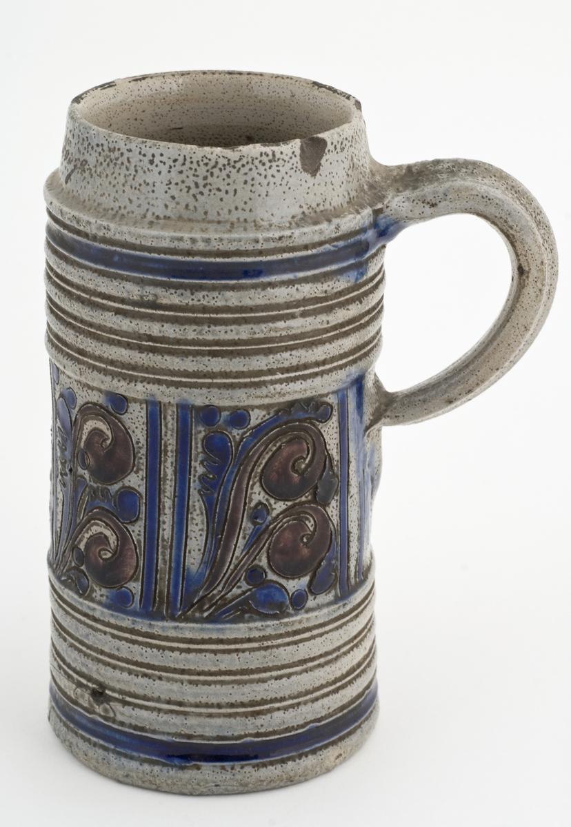 """Krus i grå keramikk av en type som stammer fra Westerwald-området i Tyskland. Karakteristisk er risset og semplet dekor og pålagte relieffer, farget med koboltblått og senere også manganfiolett, under klar saltglasur. Dette lave sylinderformede kruset kalles """"Humpen"""" og ble masseprodusert gjennom hele 1600- og 1700-tallet.    Hull i hank fra lokk (ant)."""