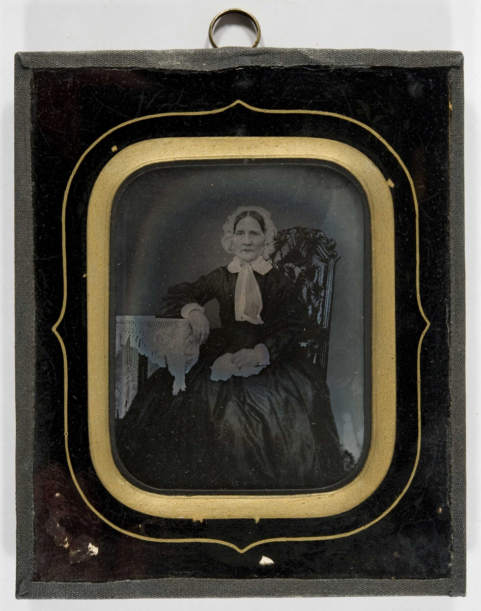 Portrett av kvinne, ukjent. Hun sitter i stol med bord som støtte for høyre arm, tilnærmet helfigur.