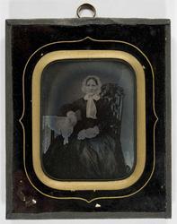Portrett av kvinne, ukjent. Hun sitter i stol med bord som s