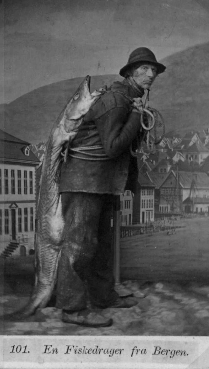 """101. Mannsdrakt, fiskerdrakt, Bergen. Portrett av fiskedrager, mann  som bærer stor laks i tau over ryggen. Fotografert i atelier med malt bakgrunn, byprospekt av Bergen. Mønstret gulvteppe. Visittkortformat. Fra serien """"Norske Nationaldragter"""" (nr.101), fotografert av fotograf Marcus Selmer (1819-1900), Bergen."""
