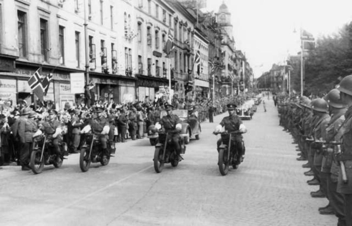 Fra Oslo under fredsdagene i 1945. Den 13.mai kommer Kronprins Olav tilbake.Kortesjen kjører oppover Karl Johans gate i retning Slottet.