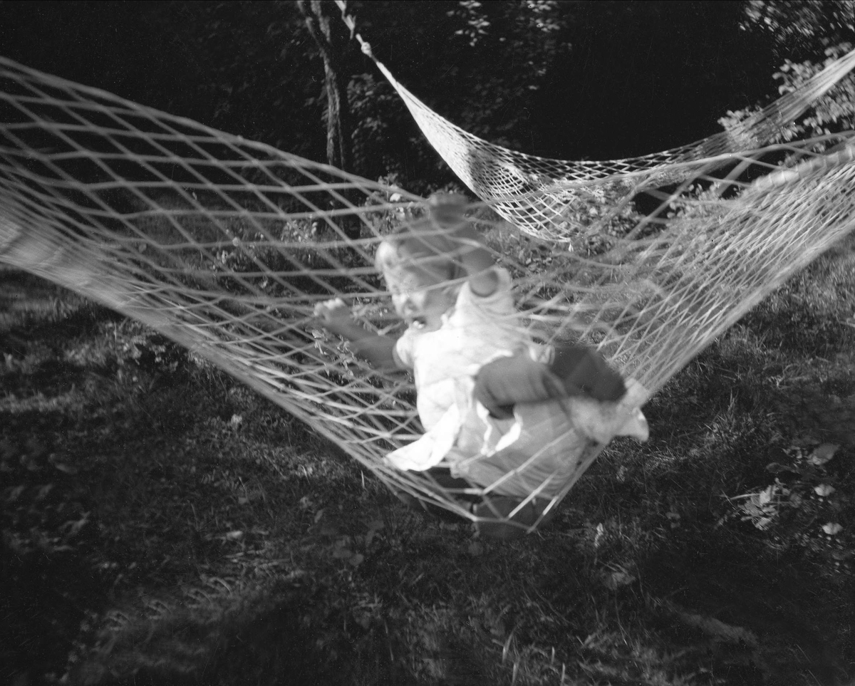 En jente leker i en hengekøy. Robsahm og Lund.